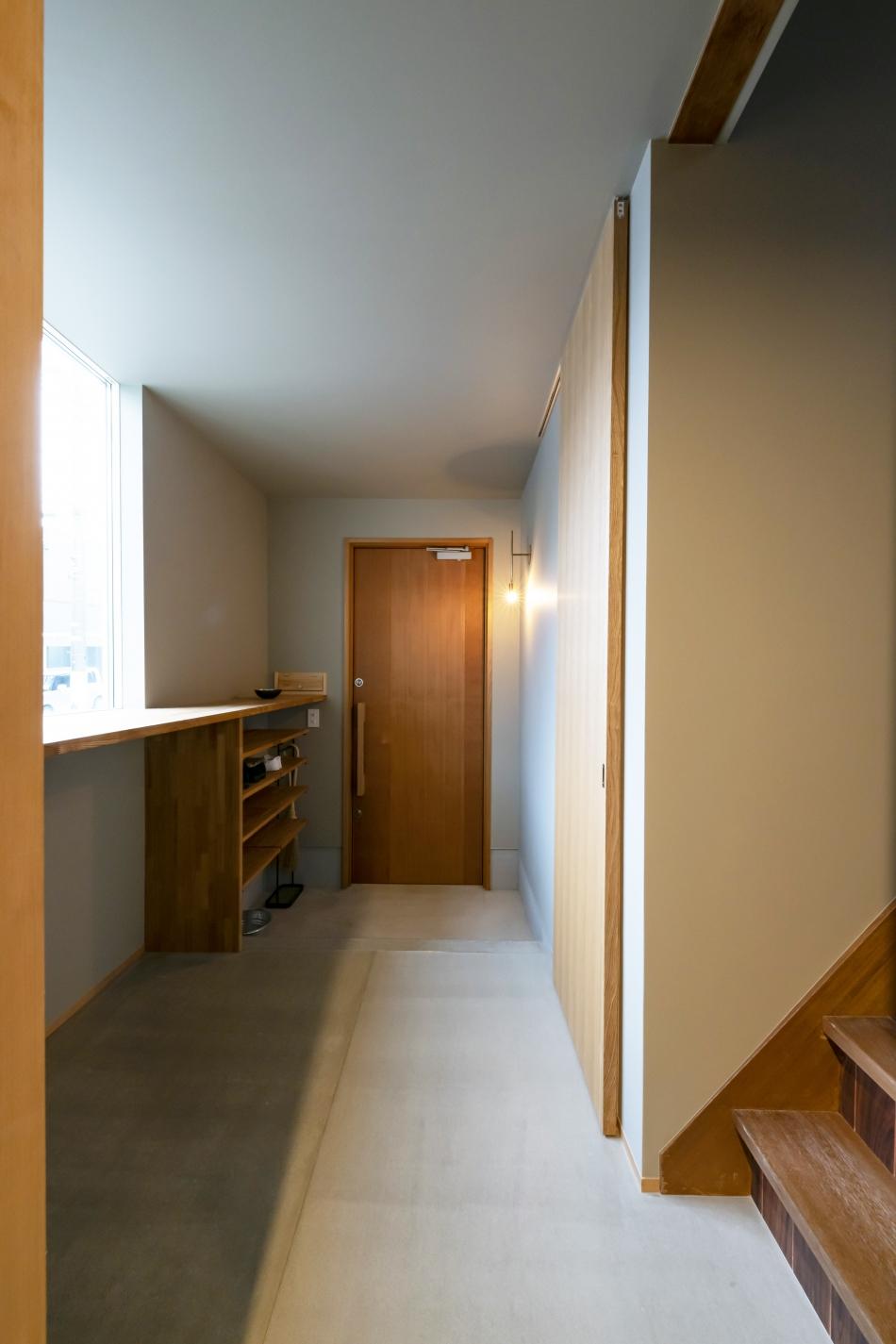 造作の玄関扉と玄関土間、モルタル風に仕上げた廊下はシンプルでモダンな空間