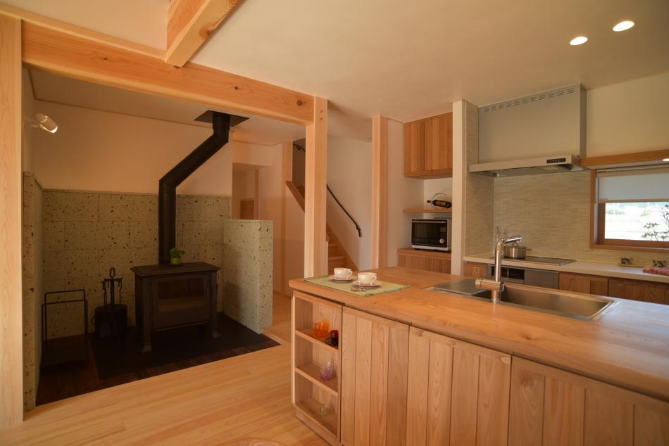 温かみある木製キッチンと存在感ある薪ストーブ